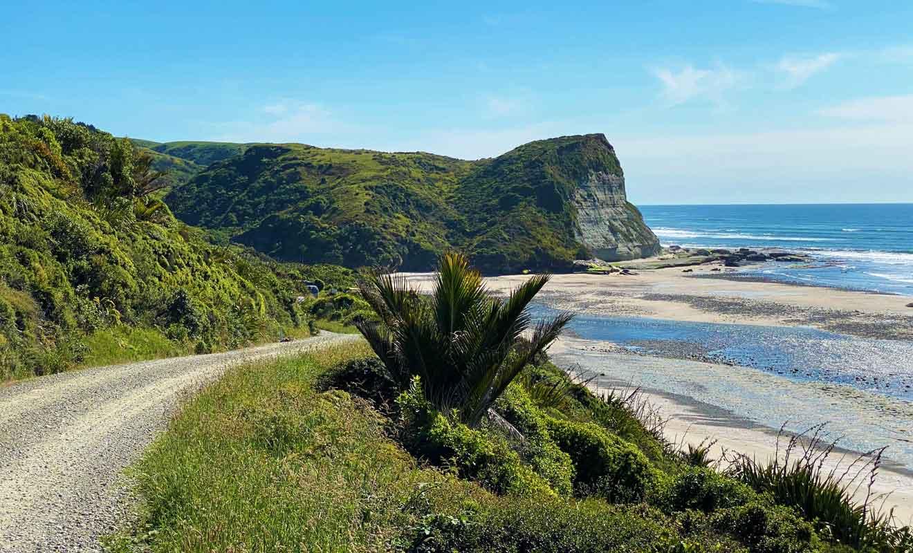 La route rejoint des plages désertes bordées de falaises.
