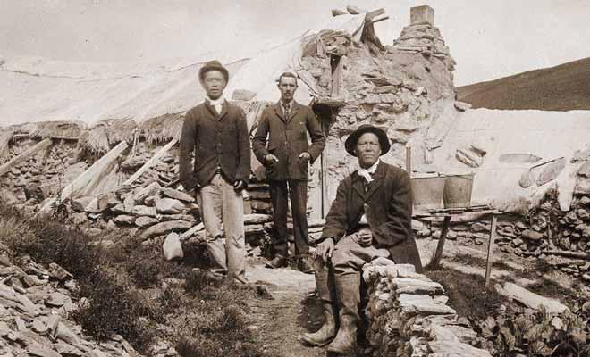 Deux Chinois et un riche propriétaire de la région photographiés devant leur maison.