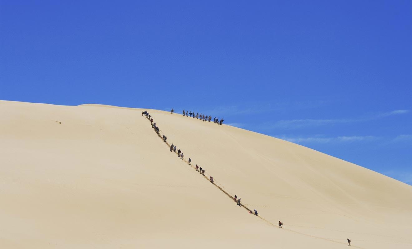 Une fois au sommet d'une dune, on peut glisser sur une planche de bodyboard pour redescendre à toute allure !