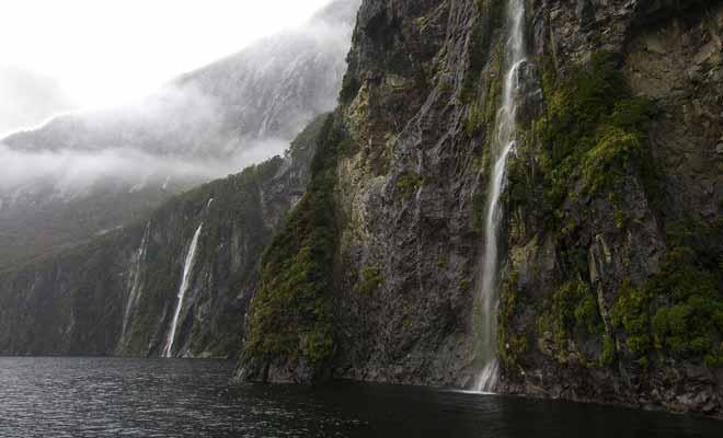 Lorsque la pluie cesse et qu'une éclaircie révèle le paysage, on découvre des centaines de cascades qui se déversent dans les eaux sombres du fiord.