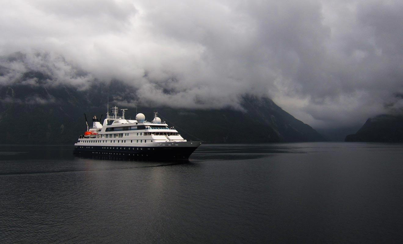 Des navires de croisières sillonnent les eaux du fiord en compagnie de quelques voiliers.