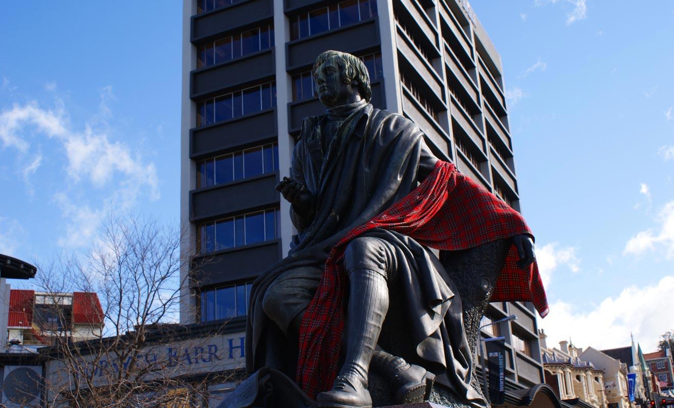 Robert Burns est un poète écossais dont la statue orne la place de l'Octagon. La légende veut qu'il tourne le dos à l'Église anglicane pour surveiller le pub de l'Oban Hotel. Si le pub a disparu, la statue est restée.