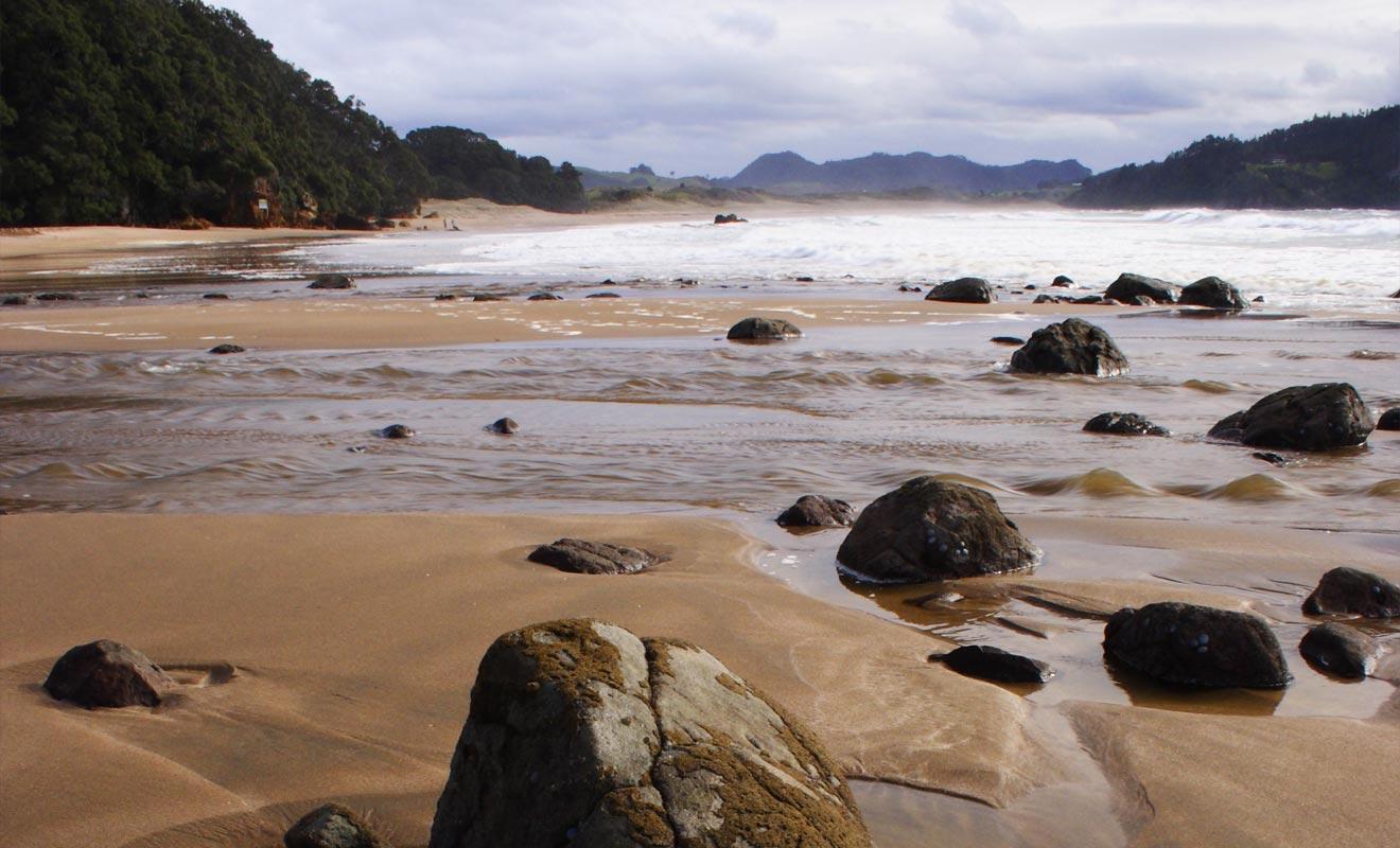 La source remonte à la surface à partir d'une faille située près des rochers de la plage.
