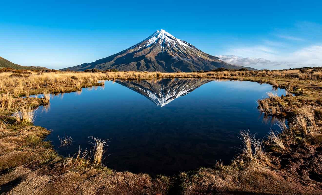 Le volcan se reflète dans les eaux calme du petit lac alpin.