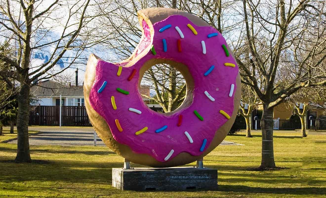 La première version du beignet géant fut incendiée puis remplacée par un simple pneu peint en rose avant qu'une statue définitive ne soit installée.
