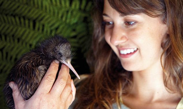 Joven mujer sosteniendo un kiwi en la mano.