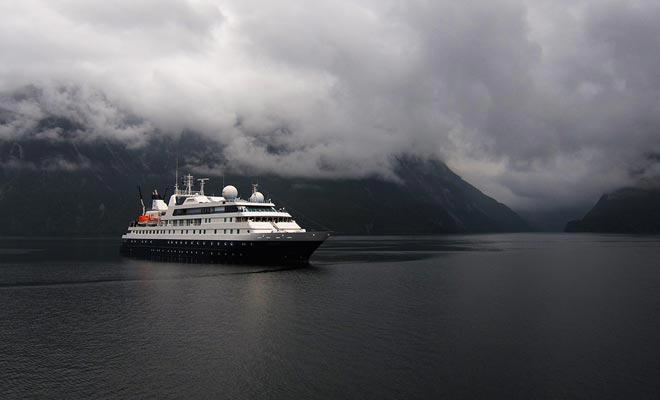 Kruisjes oversteken de wateren van het fjord met een paar zeilboten.