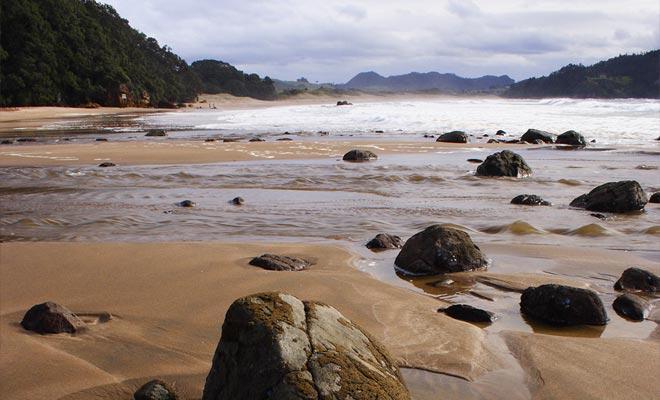 De bron stijgt naar het oppervlak van een fout in de buurt van de rotsen van het strand.