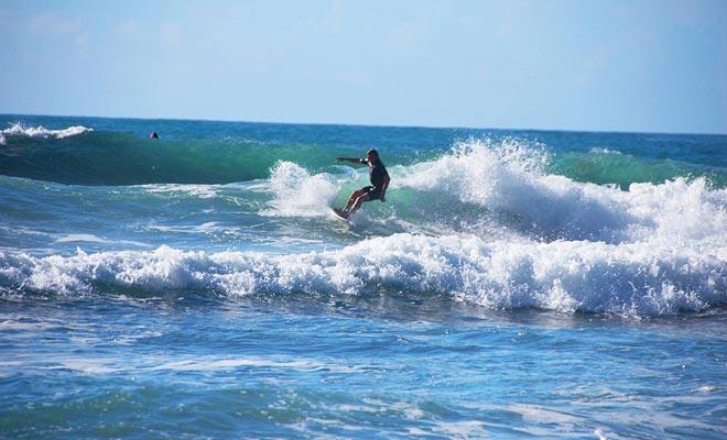 Playa de agua caliente atrae a los surfistas. No sólo mirarlos con envidia y firmar para tomar una lección.