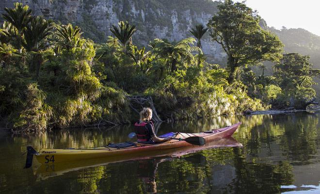 Door de Pororari rivier af te dalen door kajakken in het Nationaal Park Paparoa, kunt u prachtige landschappen waard zijn van Jurassic Park.