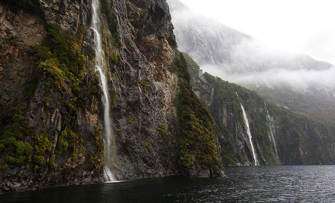 La región de Fiordland recibe un promedio de 7 metros de lluvia cada año. Cientos de efímeras cataratas evacuan el desbordamiento de agua de lluvia en fiordos como el Milford Sound.