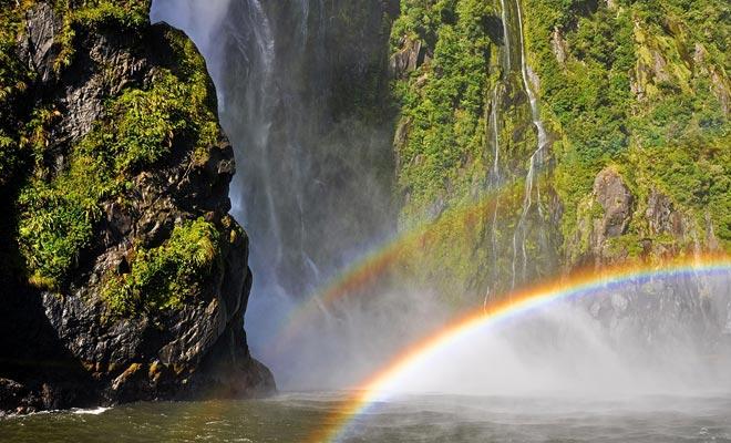 De honderden watervallen die ontstaan door de regen worden door de wind geveegd. Vocht in de lucht onthult veel regenbogen.