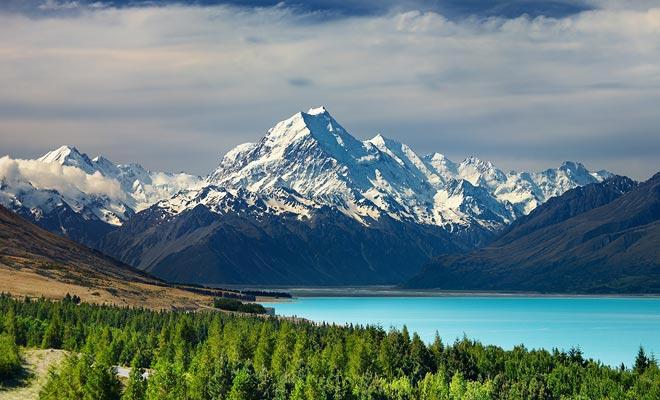 A partir de Twizel, un camino corre a lo largo del lago Pukaki hacia el pueblo Hermitage. El lago turquesa refleja el monte nevado Cook.
