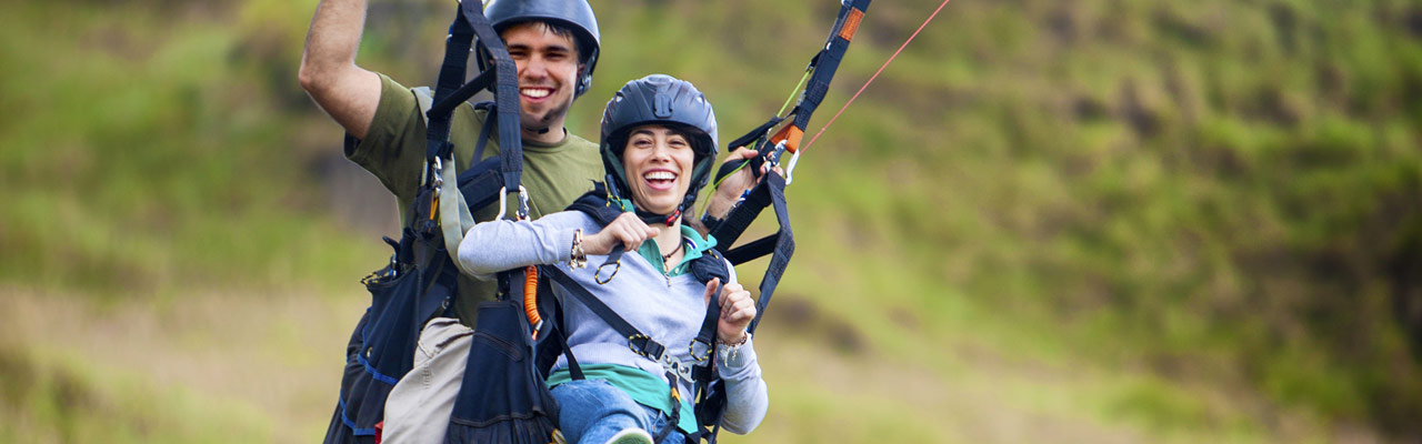 A couple enjoying paragliding in tandem in New Zealand.
