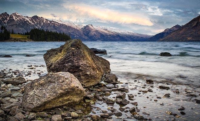 De toppen van de bergen rondom Lake Wakatipu zijn nog steeds in de vroege lente gesneeuwd.