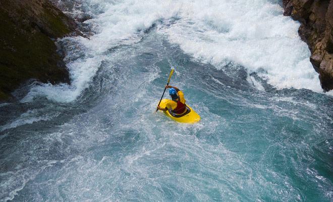 Als u in het water valt tijdens een rafting in Nieuw-Zeeland, wordt u opgesteld door een monitor die u met kajak volgt.