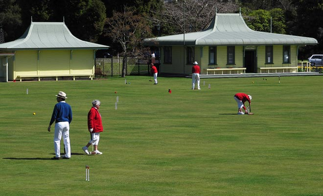 La gente juega esencialmente el croquet o las pelotas en los céspedes del jardín del gobierno. Siéntese en un banco e intente adivinar las reglas del juego viendo a los participantes vestidos.