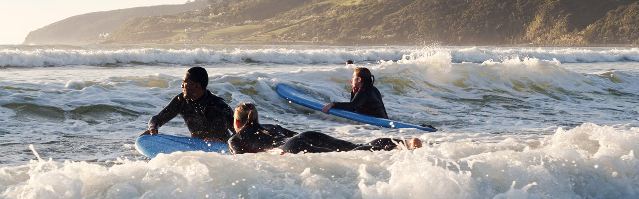 Young people taking a surfing lesson.