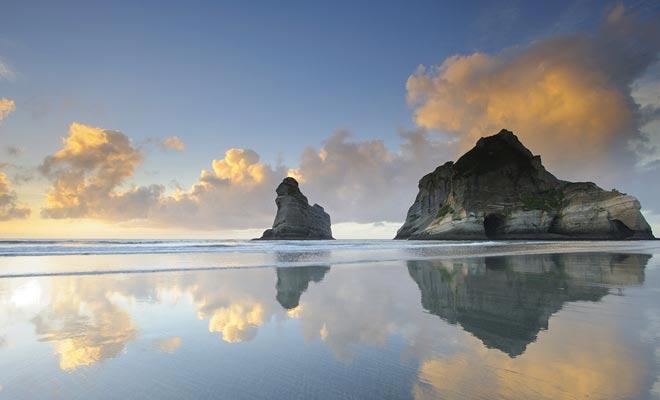 La playa de Wharariki es una de las playas más hermosas del país. En la madrugada, el reflejo de las rocas sobre la arena húmeda es notable.