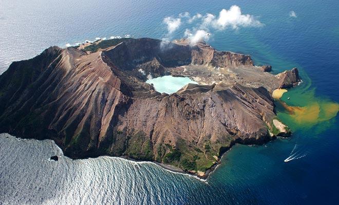 De zwavel die uit de vulkaan van het White Island stroomt, kleuren de zee in geel.