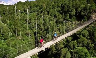 Con su bicicleta, cruce los puentes colgantes durante hermosas caminatas.