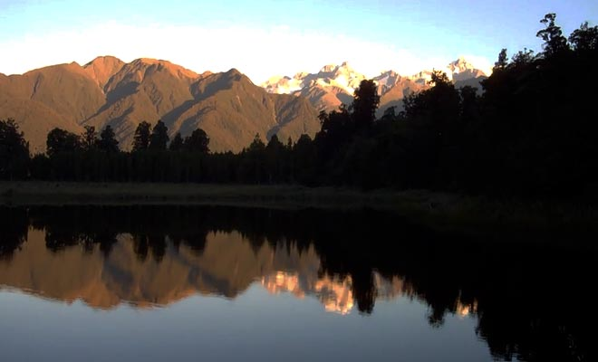 Le reflet des montagnes s'explique par la couleur du fond du lac. Le reflet est saisissant et l'on se croirait devant un miroir.